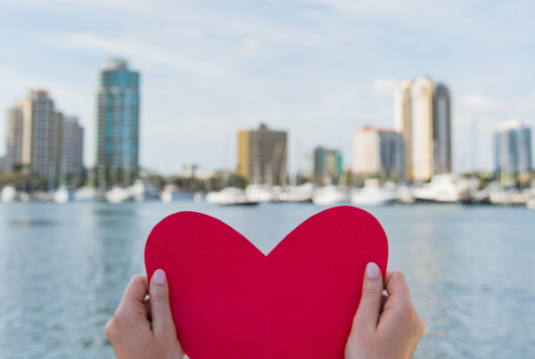 Woman holds piece of red paper shaped like a heart in front of St. Petersburg, Florida skyline and ocean