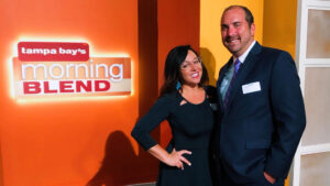 Lisa Williams, President of Evolve & Co, and a client standing in front of Tampa Bay's Morning Blend Sign