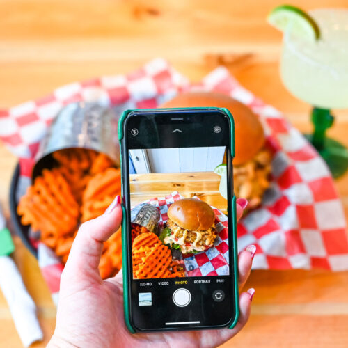Phone taking a photo of a burger at the Boulevard Burgers and Taphouse
