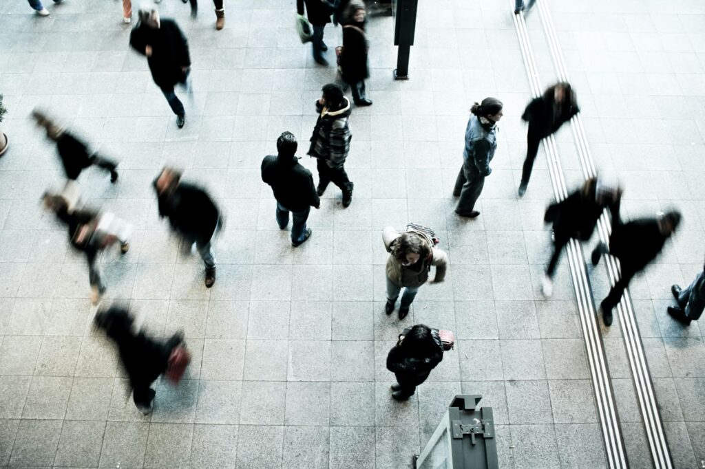 Blurred image of people walking in public place to represent demographics